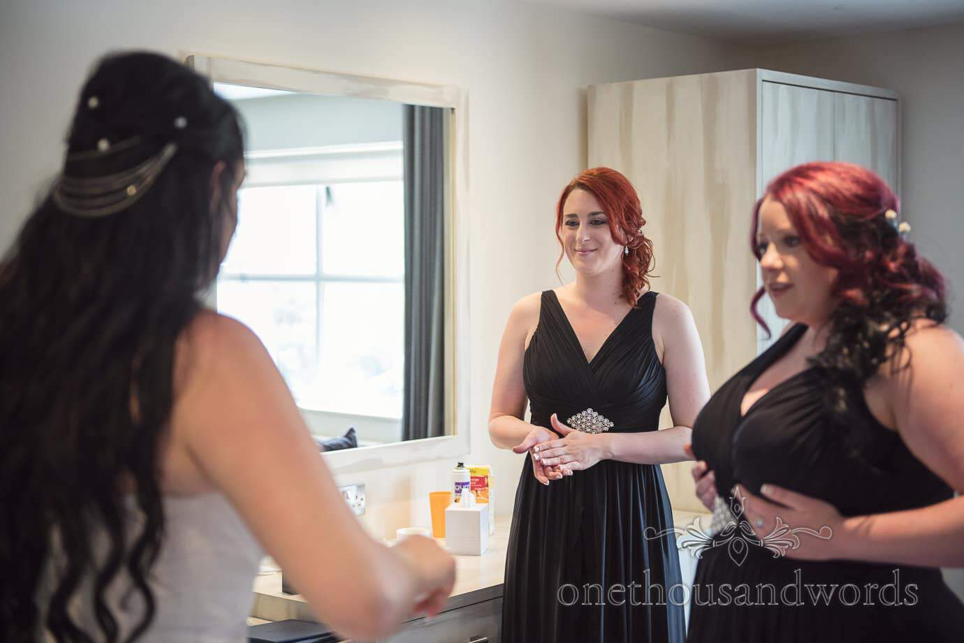 Red head bridesmaids in black bridesmaid's dresses at rock and roll wedding preparations