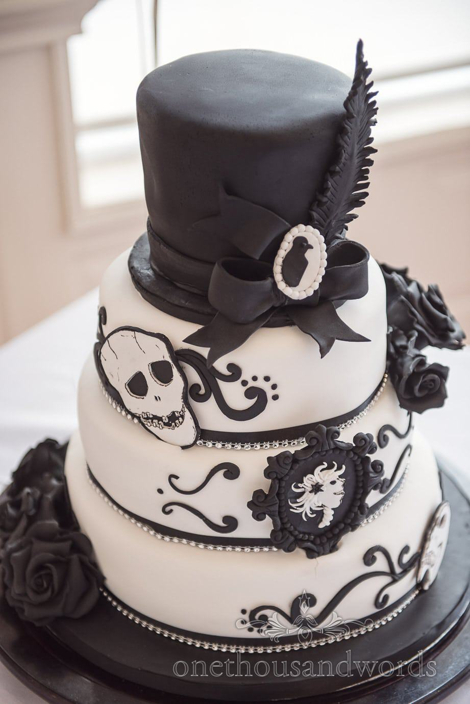 rock and roll themed Black and white wedding cake with black roses, skull and top hat