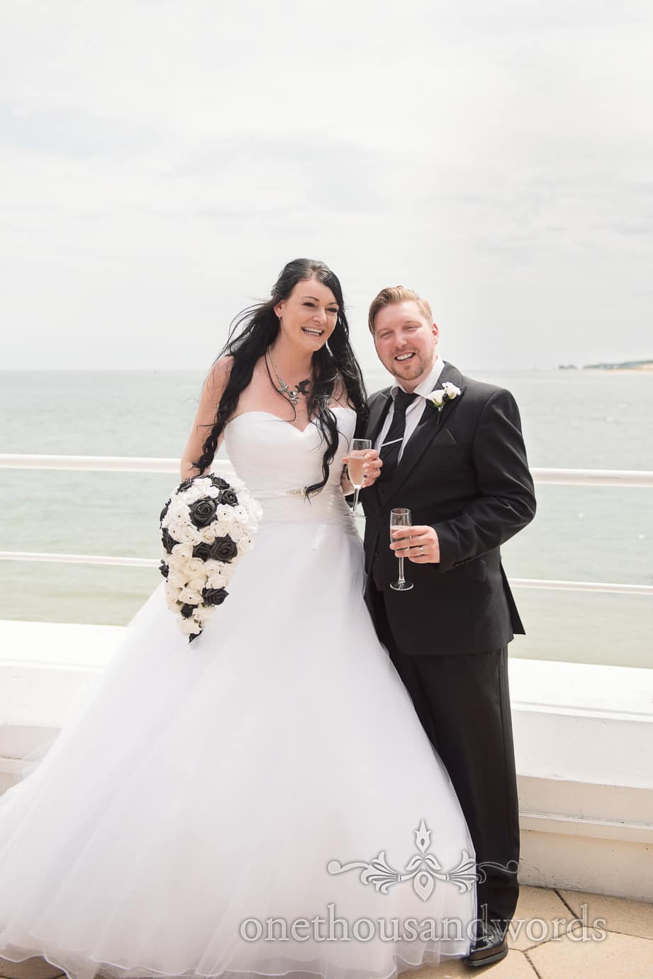 Rock and Roll wedding bride and groom in black and white laughing by the sea