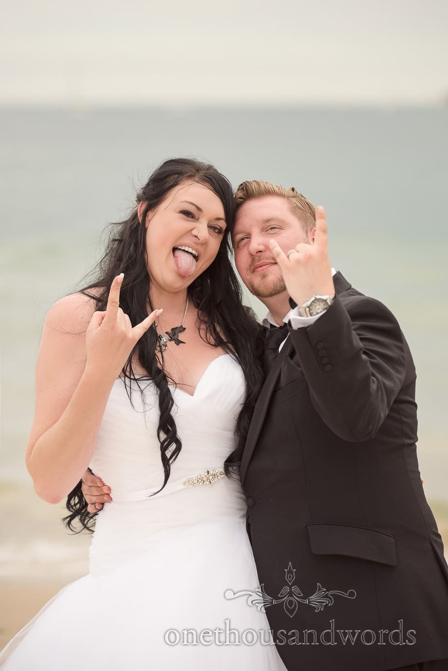 Rock and roll wedding bride and groom in black and white with rock hands by the sea