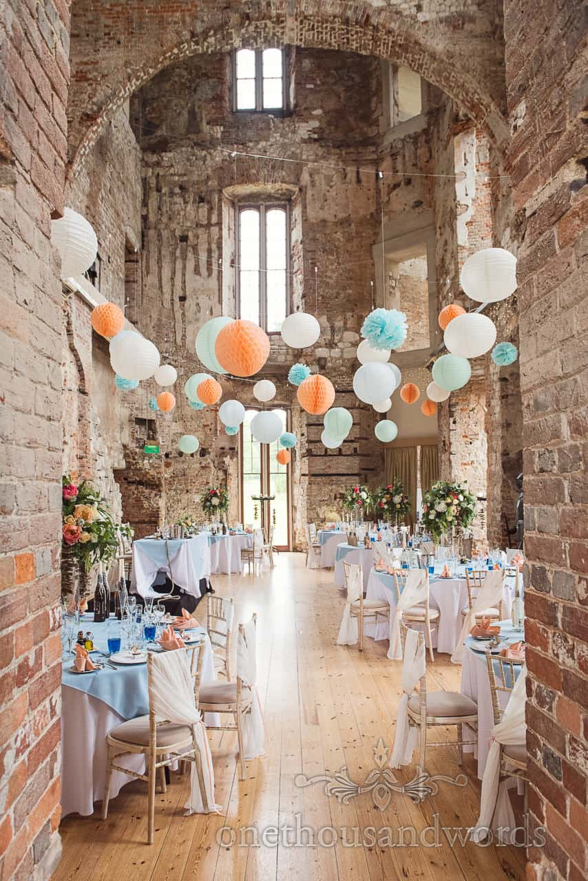 Ruined castle hall wedding breakfast set up with orange and blues at Lulworth Castle wedding