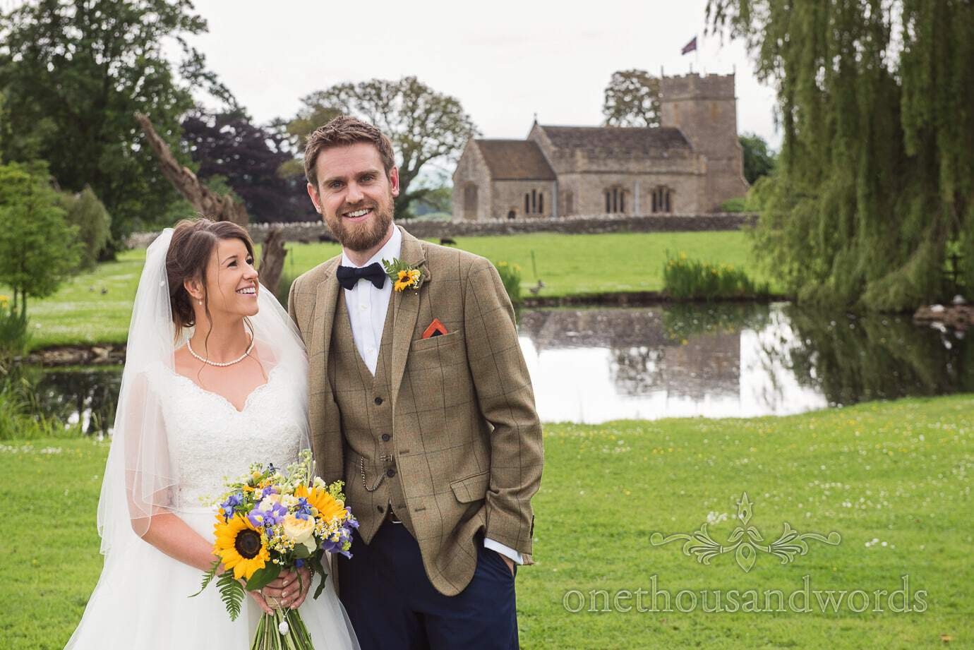 Rustic bride and groom with English countryside pond and stone church in background