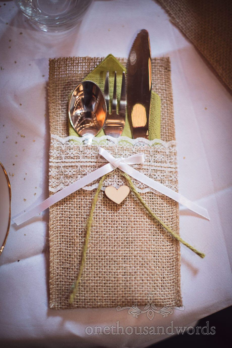 Rustic wedding cutlery place setting with hessian, lace, ribbon and golden sprinkles