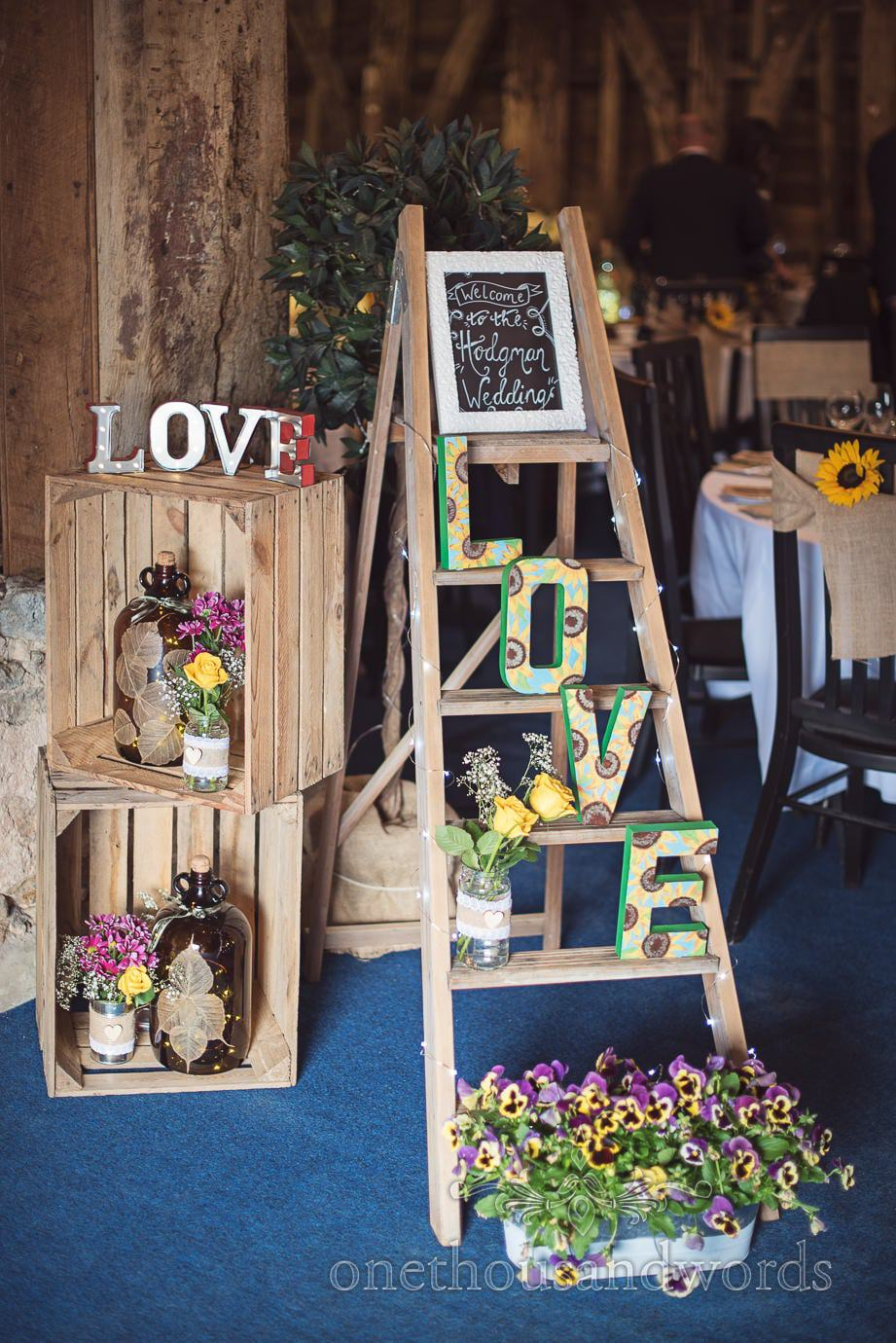 Rustic wedding signs with wooden step ladders, wooden crates and flower buckets