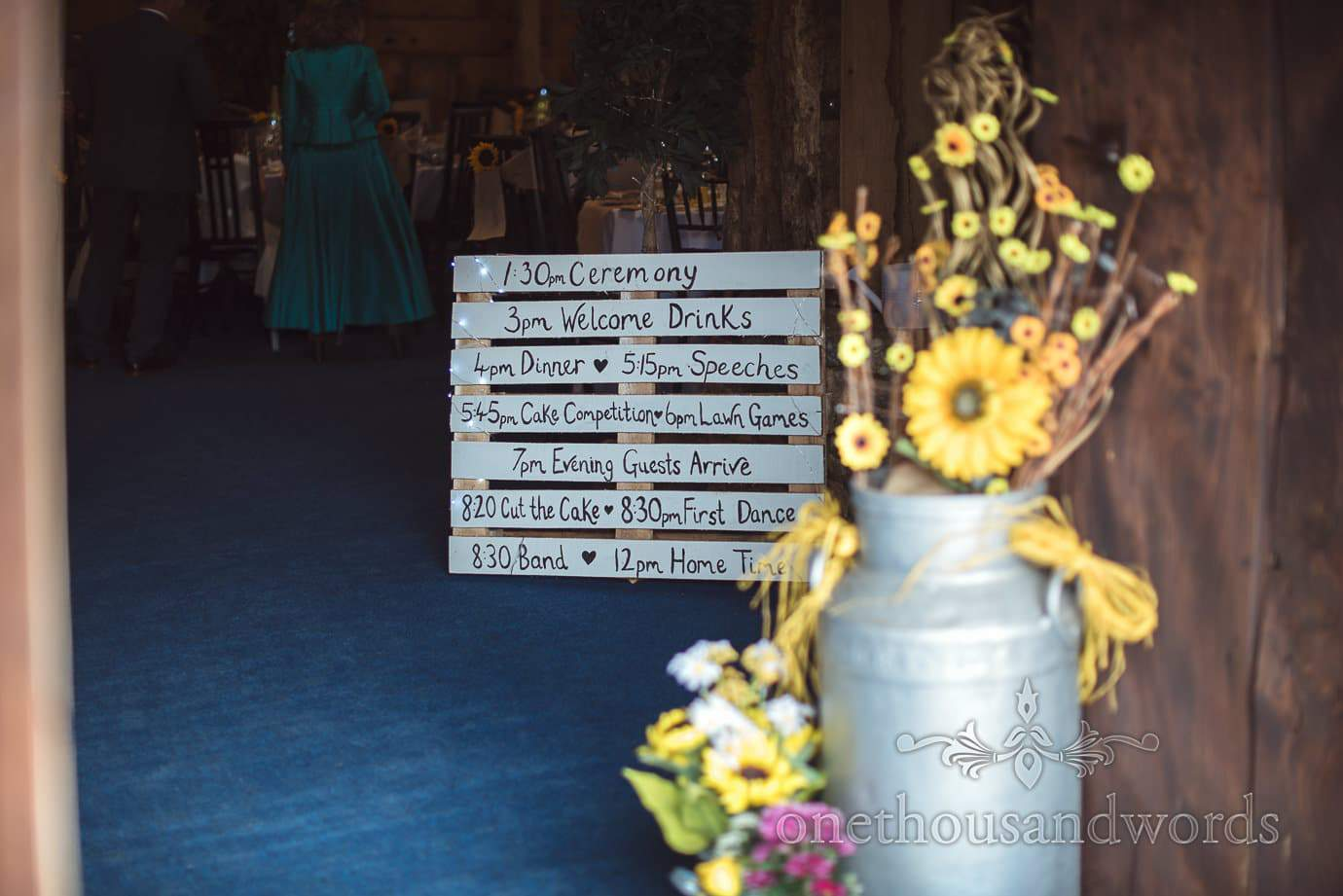 Rustic wedding timings on wooden pallet at Stockbridge Farm Barn wedding venue