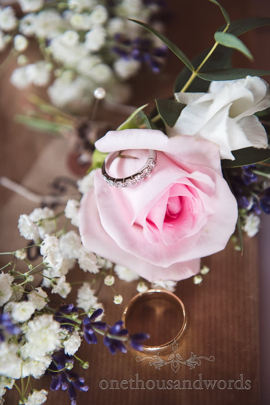 Silver diamond and gold band wedding rings with pink rose buttonhole wedding flower