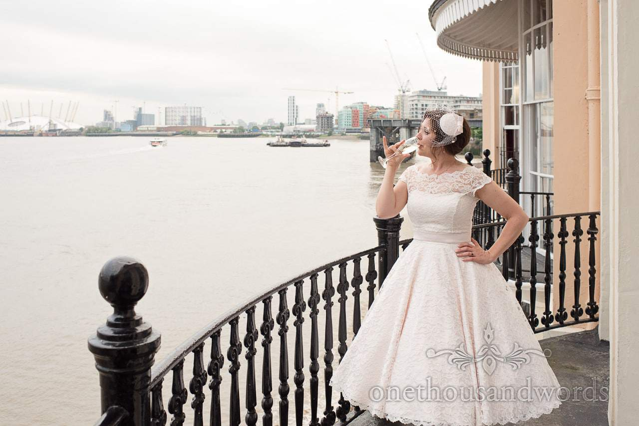 Stylish bride in 1950's style wedding dress on balcony overlooking the Thames and London