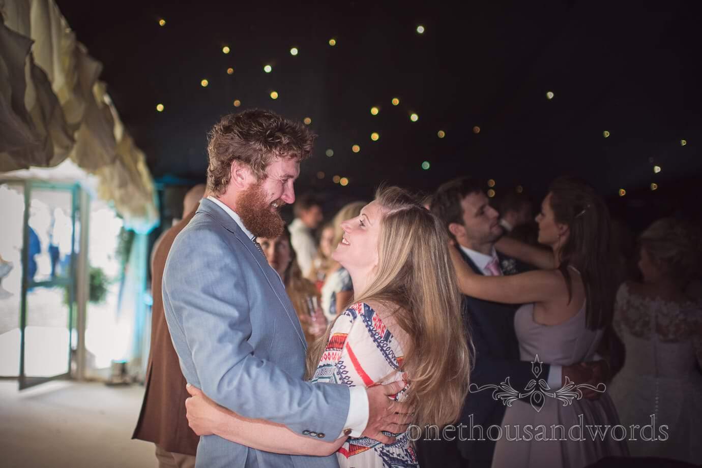 Stylish wedding guests dancing in black walled star ceiling marquee wedding dance floor