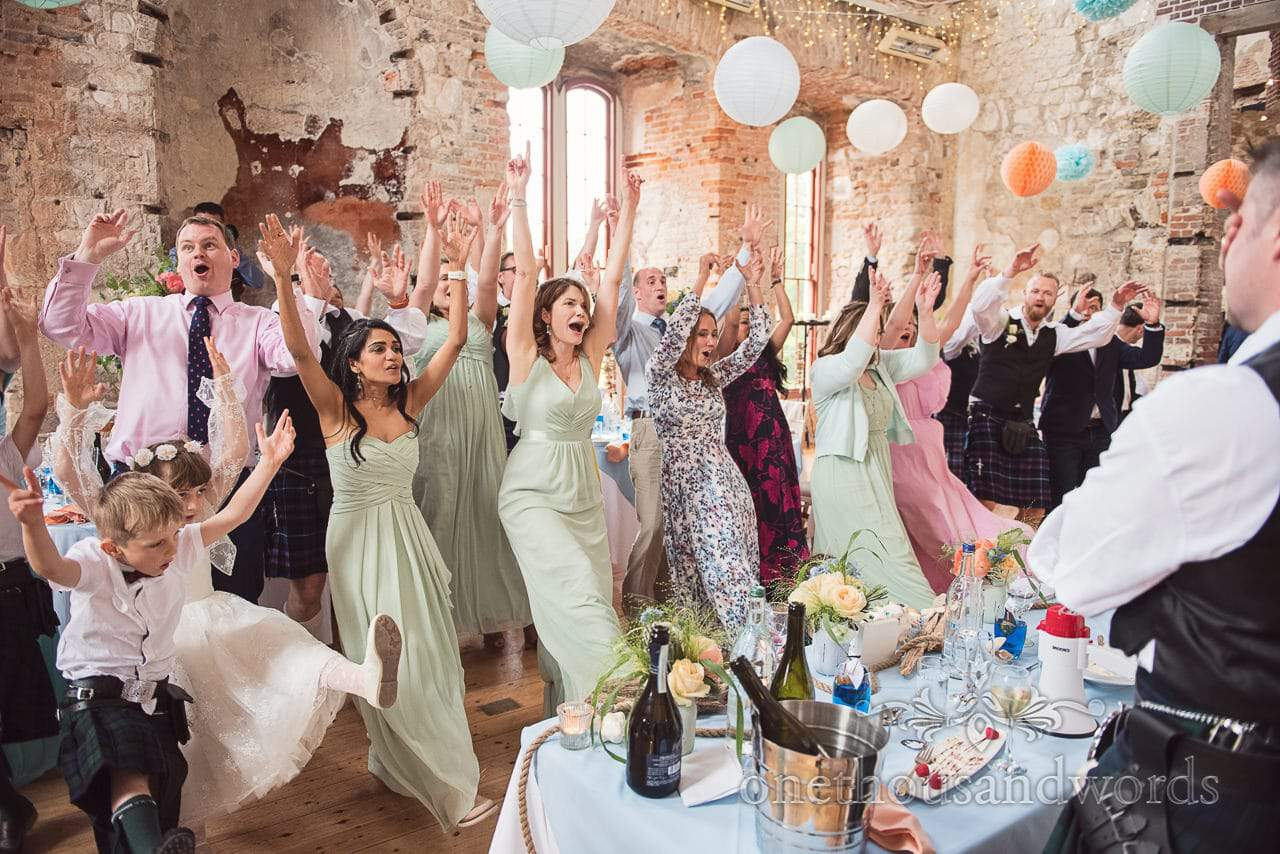 Surprise flash mob wedding party dance for bride and groom during wedding breakfast at Lulworth Castle in Dorset