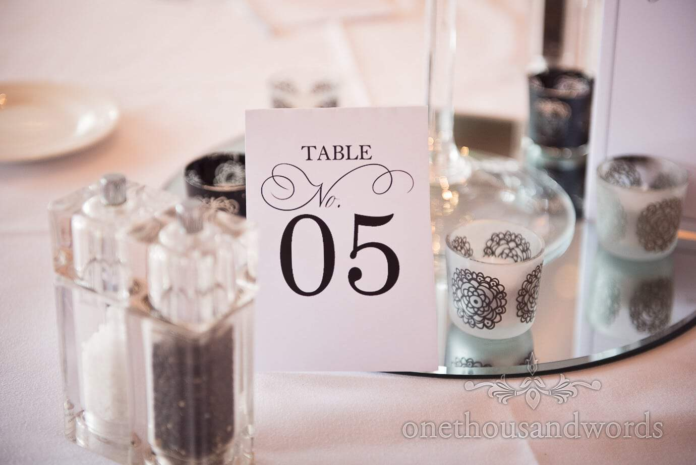 Table number sign and black and white tea light holders at rock and roll wedding