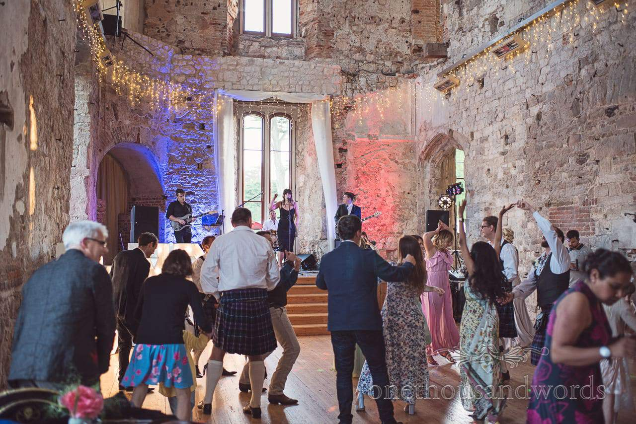 The Cover UP Band plays to dancing guests in great hall at Lulworth Castle wedding