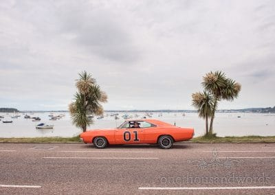 The General Lee wedding car Dukes of hazard with palm trees by the sea at Sandbanks, Dorset wedding