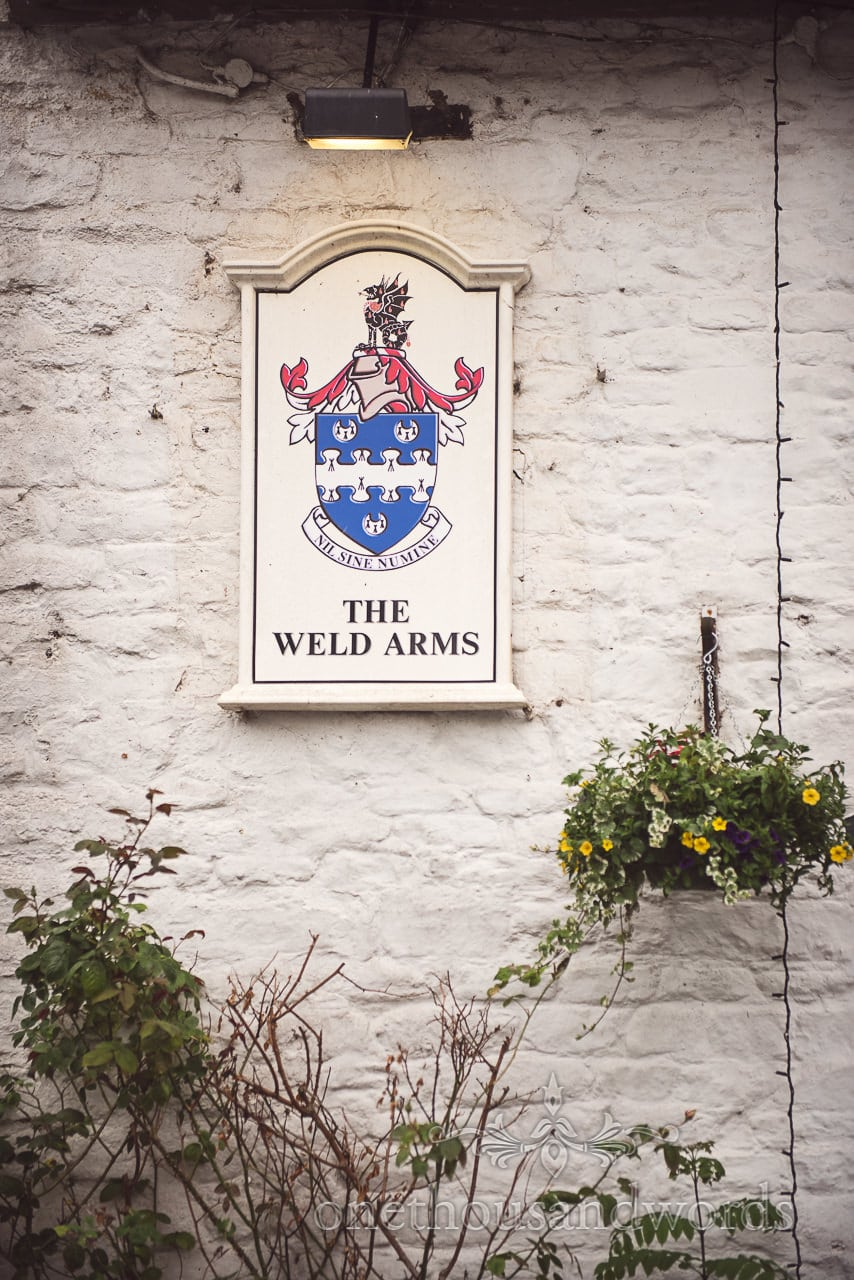 The Weld Arms pub sign on brick wall near Lulworth castle