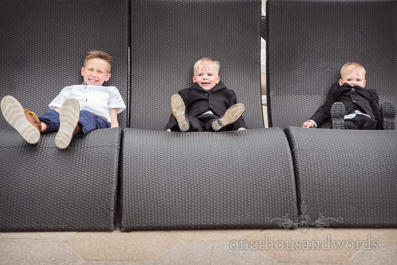 Three child wedding guests in a row on sun loungers at Haven Hotel wedding