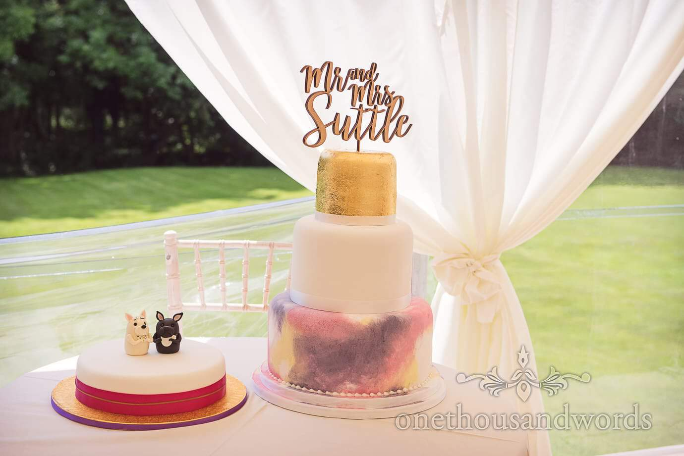Three tier gold, white and painted wedding cake with wedding dogs cake for country wedding