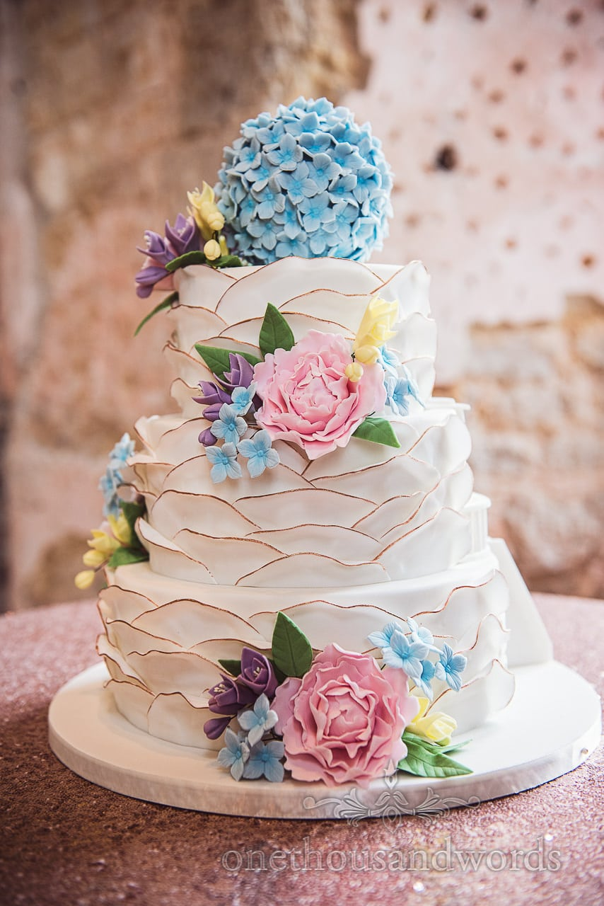 Tiered wedding cake decorated with colorful flowers at Lulworth castle wedding