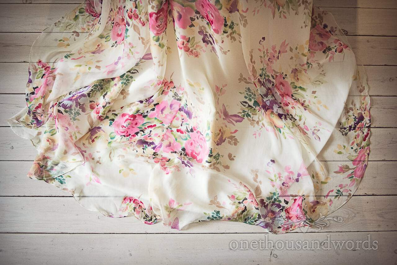 Train of floral wedding dress against wooden floor from Lulworth castle wedding dress