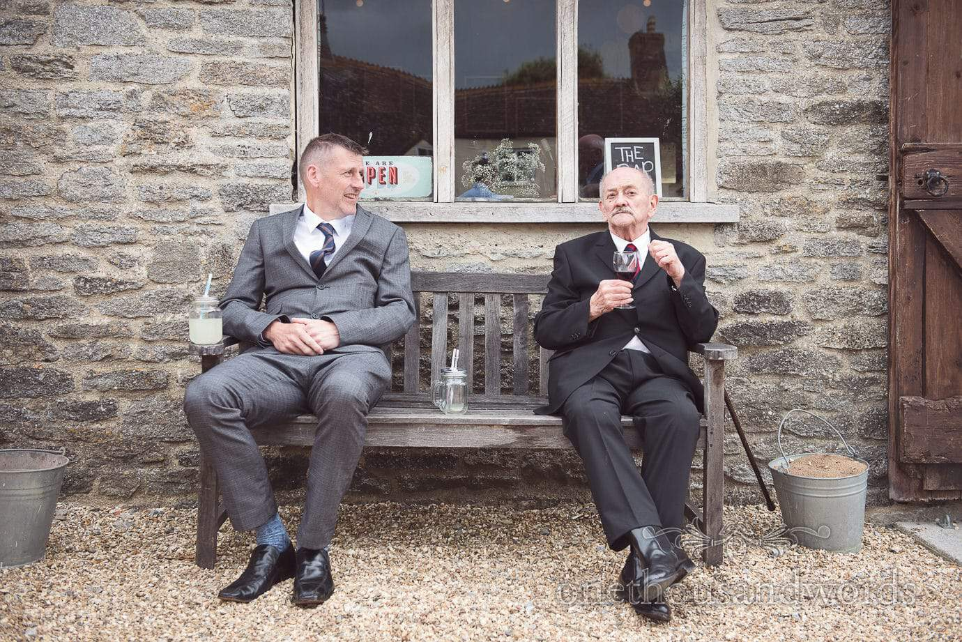 Two wedding guests take a break at rustic barn wedding