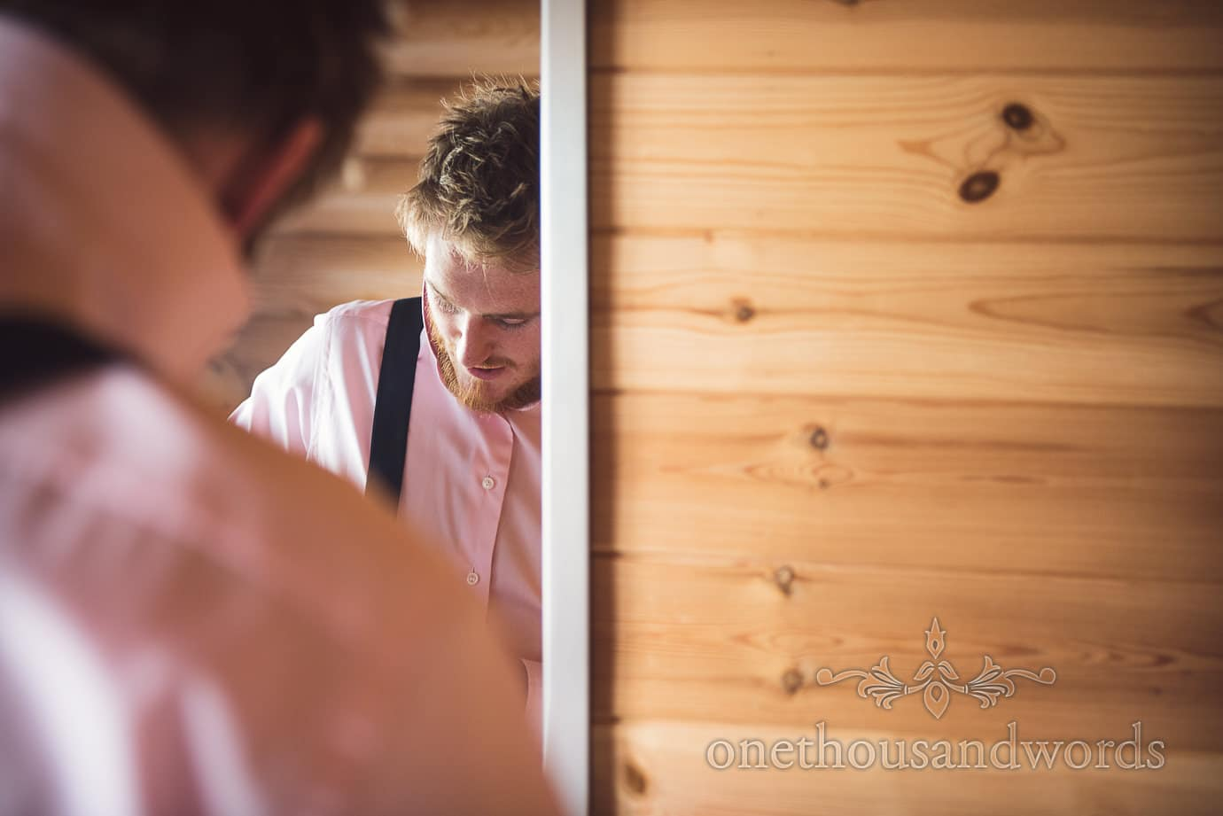 Bearded groom in pink shirt and navy braces in mirror on wedding morning