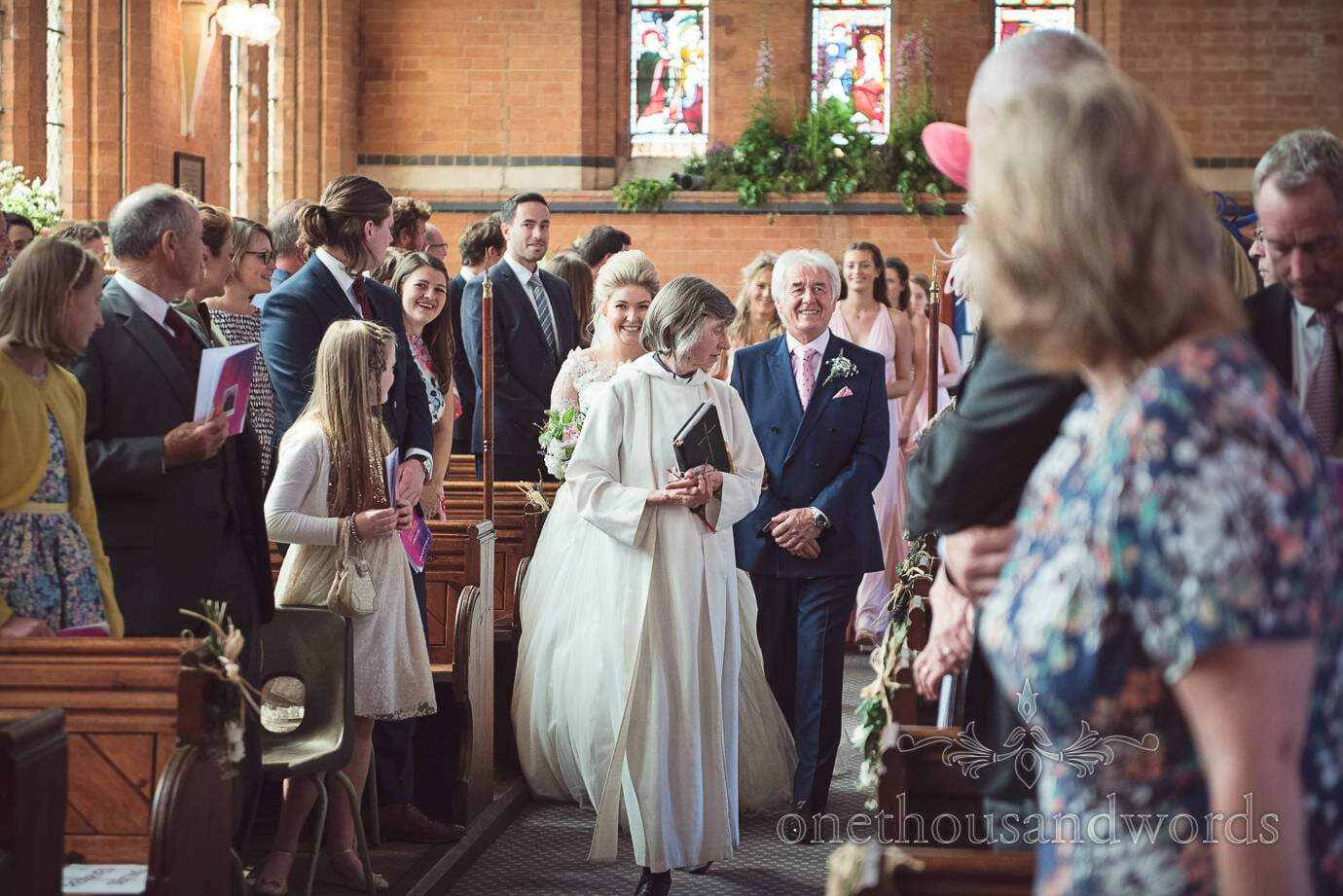 Vicar leads father of the bride and bride up aisle at church wedding in Leicestershire