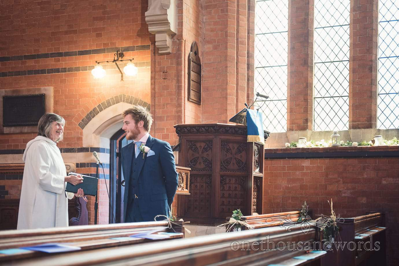 Vicar talks to groom in blue wedding suit in church before wedding ceremony