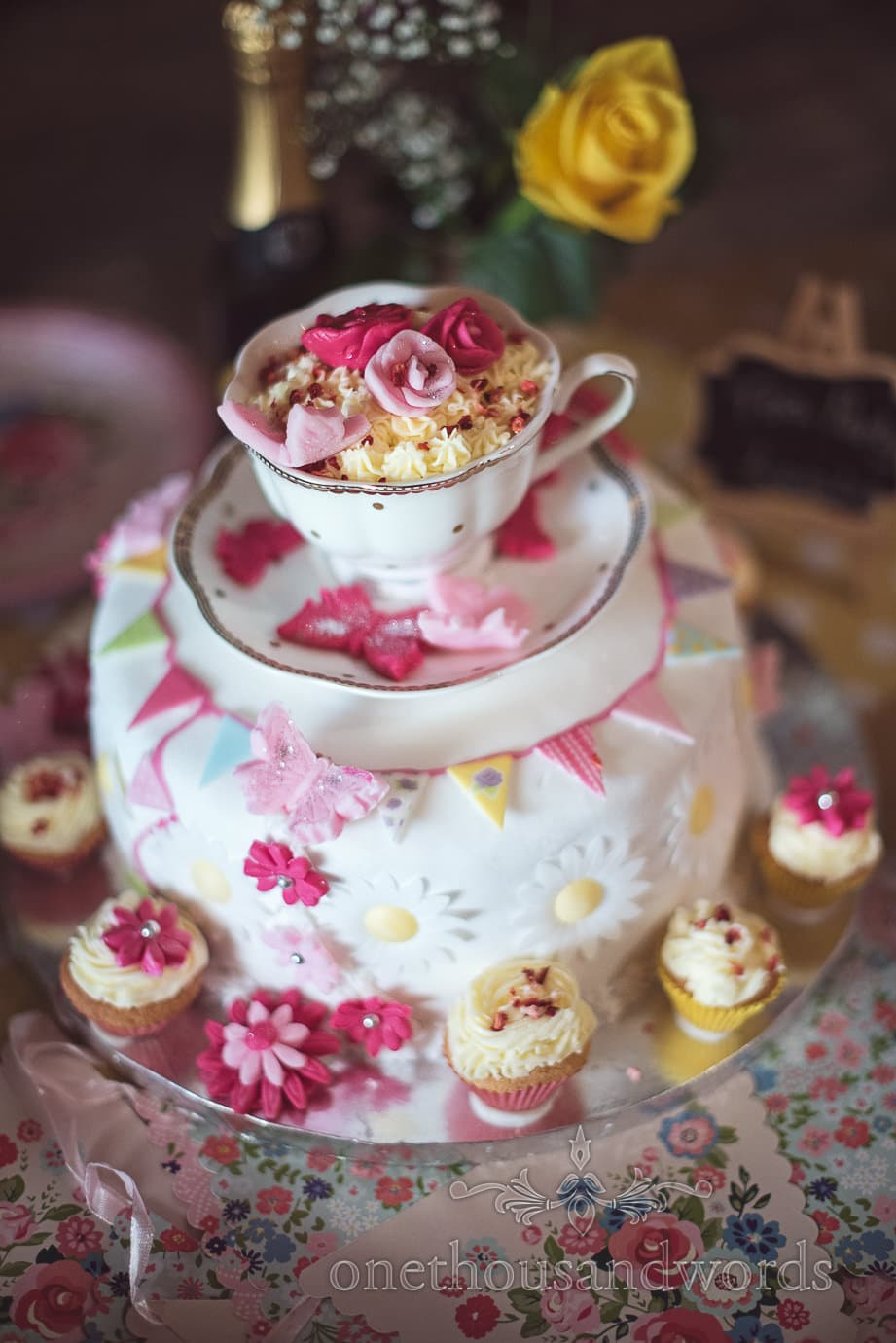 Wedding cake decorated with cup cakes, bunting and a tea cup and saucer