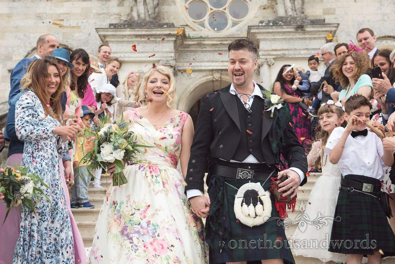 Wedding confetti bride in floral dress and groom in kilt on the steps at Lulworth Castle wedding