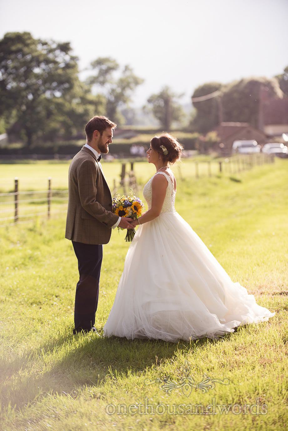 Wedding couple embrace in the afternoon sunshine at countryside rustic wedding