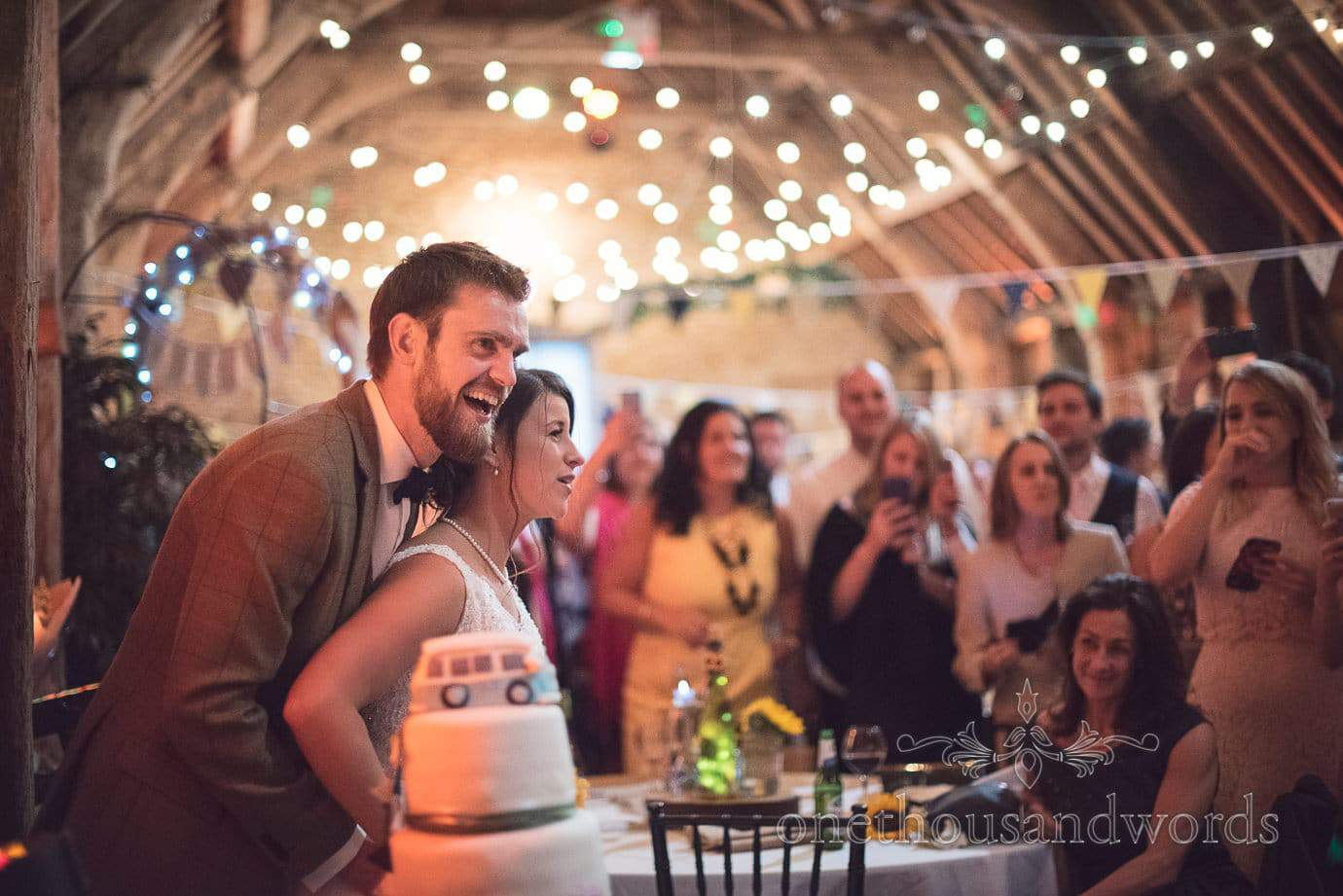 Wedding couple prepare to cut the cake in wooden fairy lit barn at rustic wedding