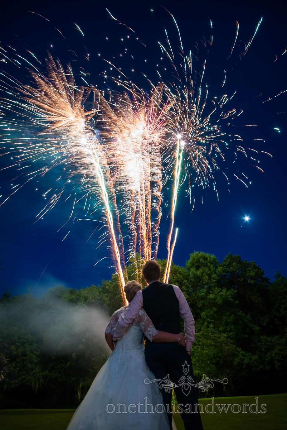 Wedding fireworks above trees with bride and groom in foreground and moon