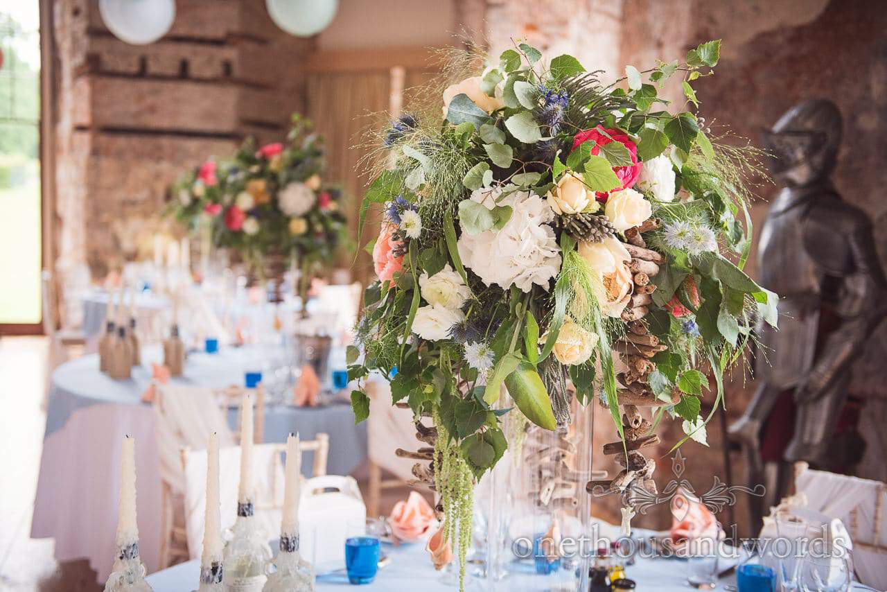 Wedding flowers table centers with suit of armour at Lulworth Castle wedding venue