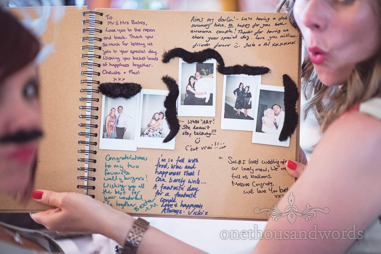 Wedding guest book with Polaroid photographs and stick on moustaches