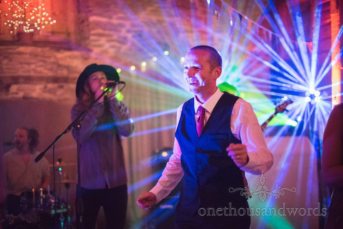 Wedding guest dances in front of wedding band and colourful lazers at Stockbridge Farm Barn