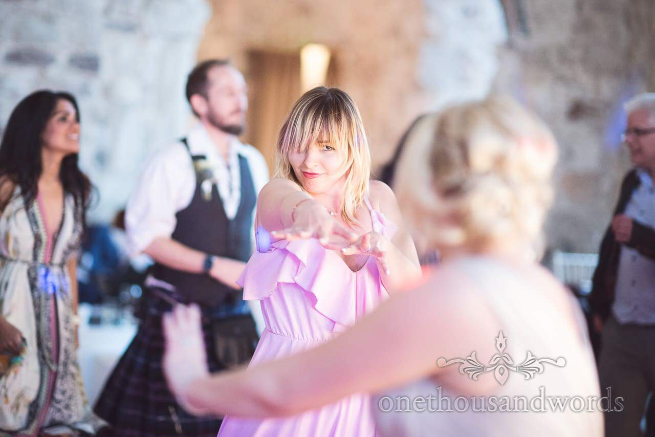 Wedding guest dancing at wedding evening reception at Lulworth Castle, Dorset