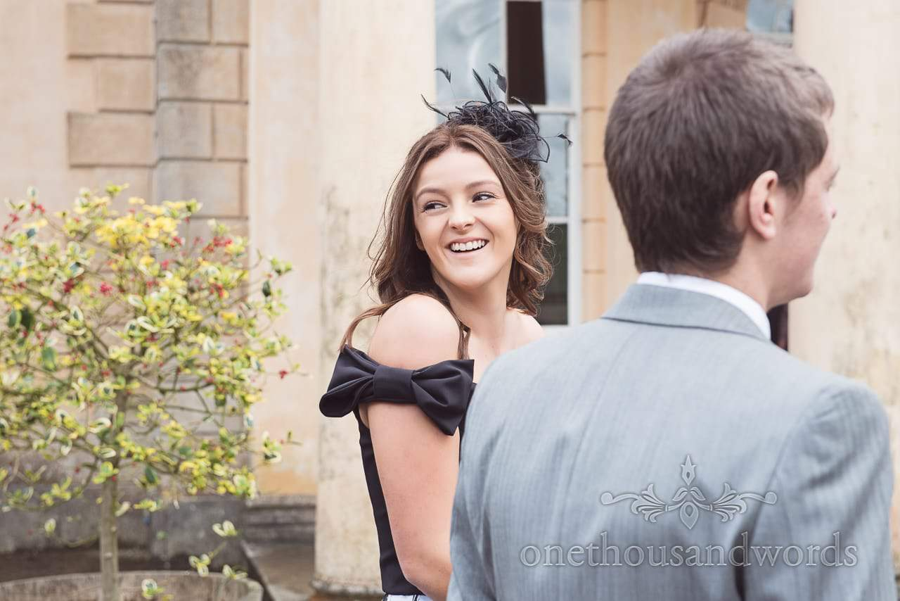 Wedding guest in black bow dress and black feather fascinator at Upton House wedding