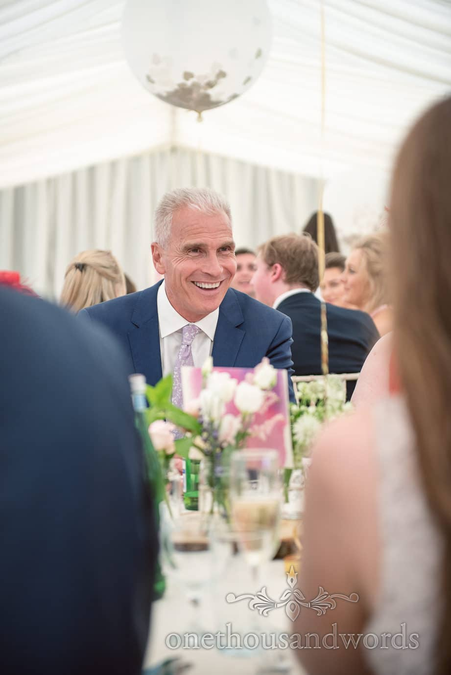 Wedding guest in blue suit laughs at wedding speeches at marquee wedding photograph