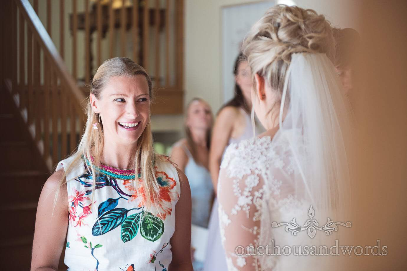 Wedding guest in bright coloured floral print dress laughs with bride