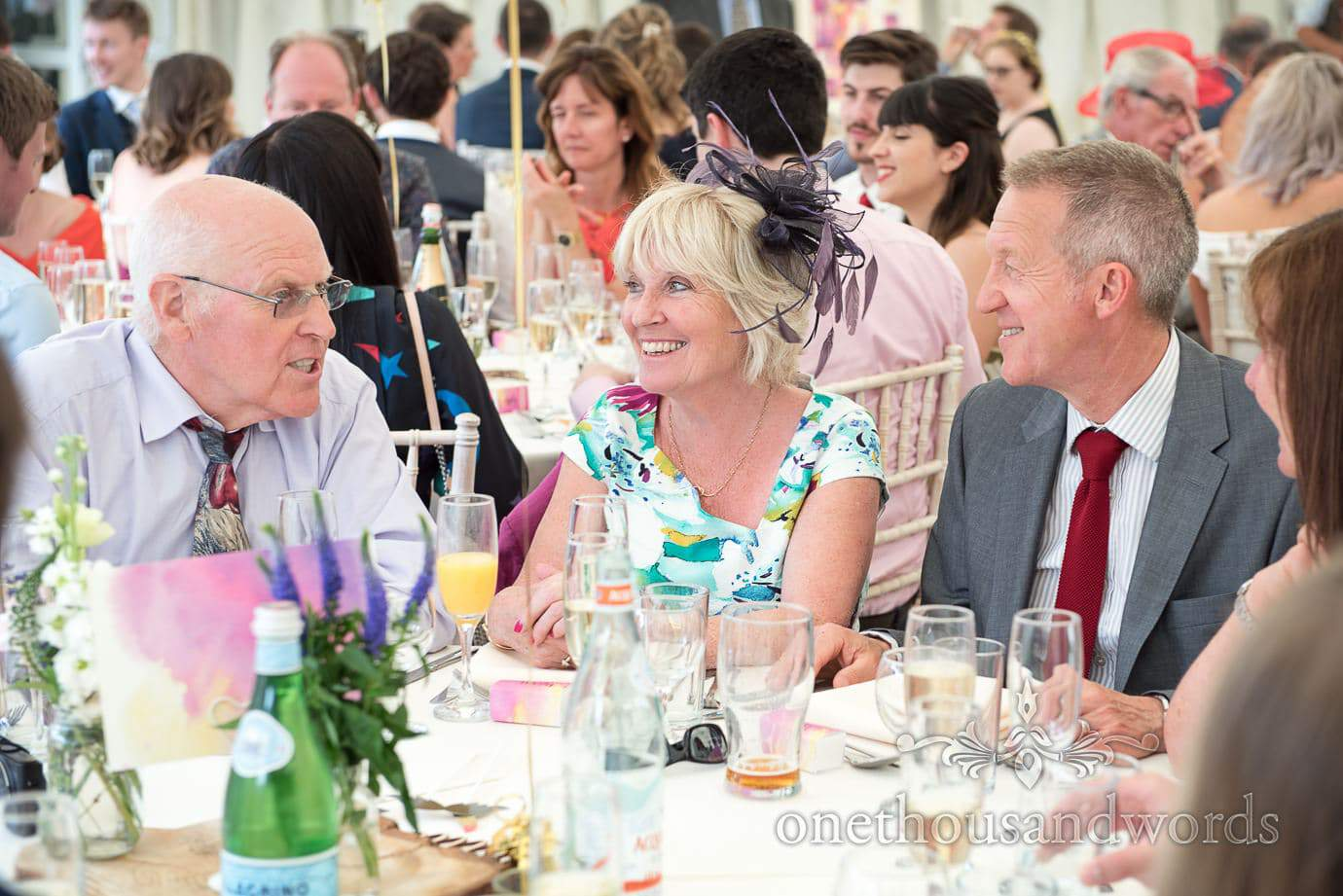 Wedding guest in colourful floral dress laughing during marquee wedding breakfast