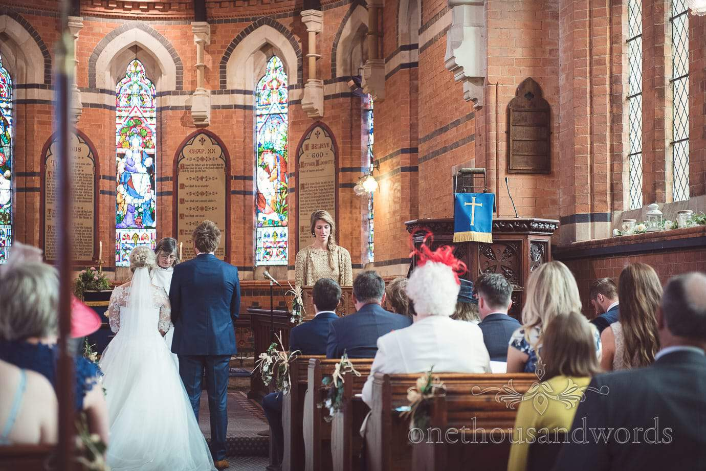 Wedding guest in gold gives bible reading at Church wedding ceremony