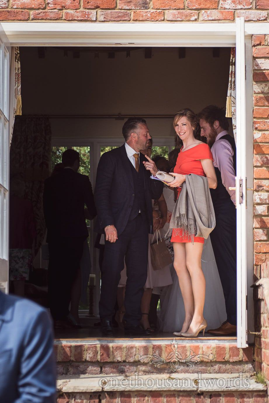 Wedding guest in red dress leaves receiving line to join country garden reception