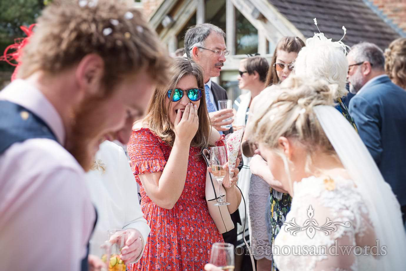 Wedding guest in red flower print dress and reflective sunglasses laughs at confetti