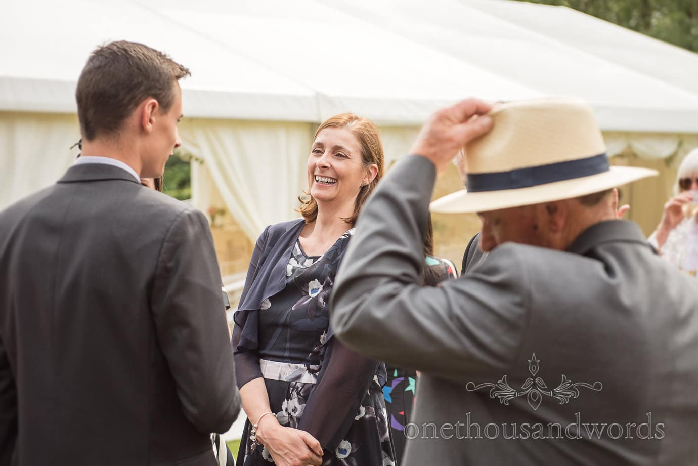 Wedding guest laughing during drinks reception in front of wedding marquee