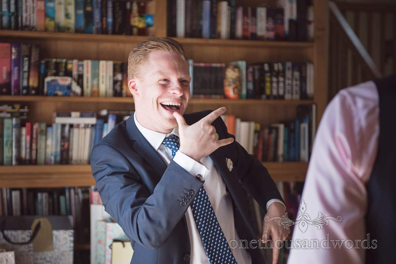 Wedding guest makes gangsta signs in front of bookshelf during receiving line