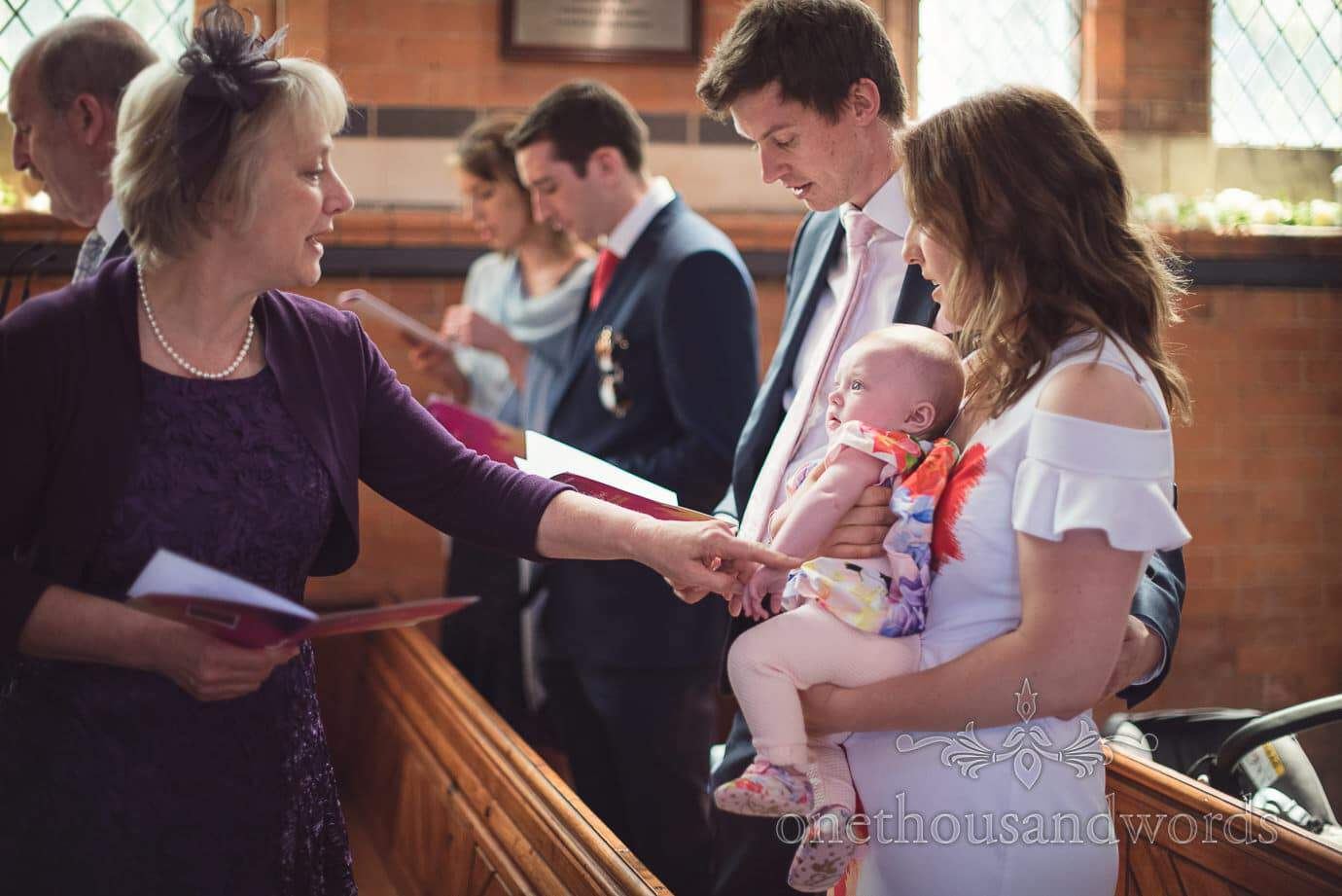 Wedding guest plays with baby at church wedding ceremony in Leicestershire