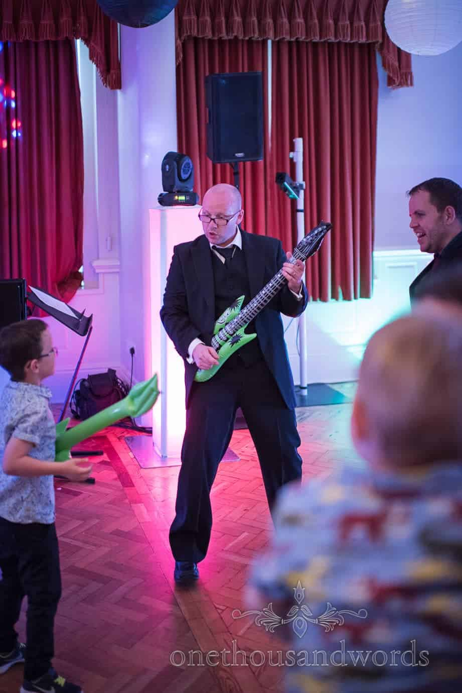 Wedding guest rocks out with inflatable guitar at Rock and Roll themed wedding