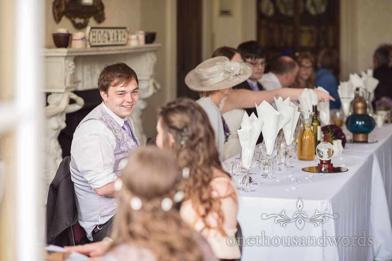 Wedding guest sits at top table at Upton House wedding in Poole