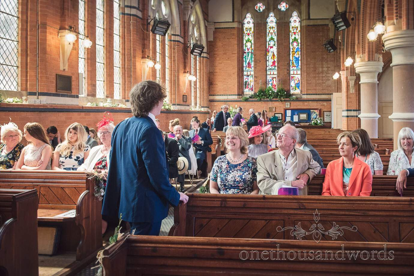 Wedding guests arrive waiting in church pews at red brick church wedding