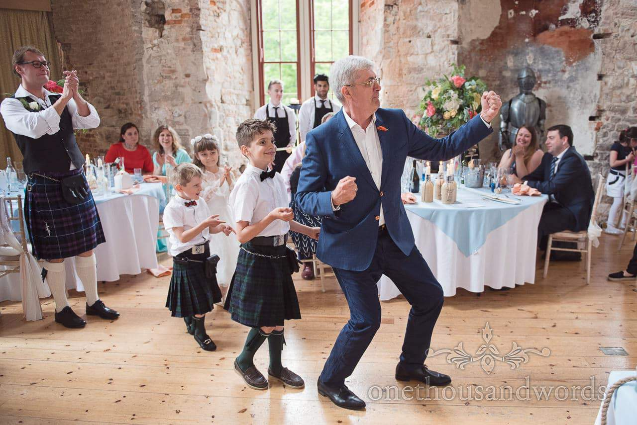 Wedding guests at kilted wedding dance around wedding breakfast at Lulworth Castle