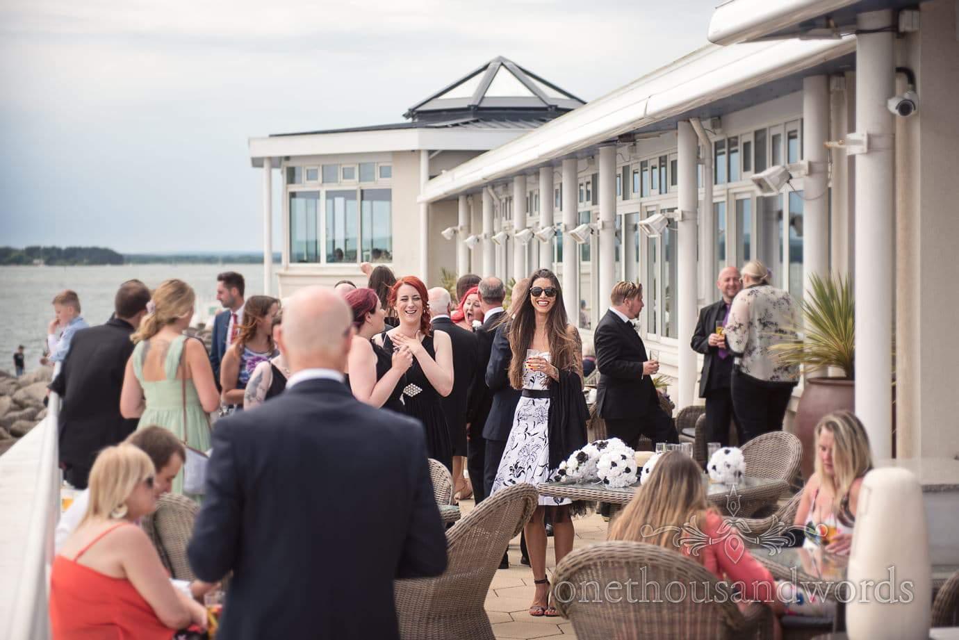 Wedding guests enjoy drinks reception by the sea t Haven Hotel wedding venue