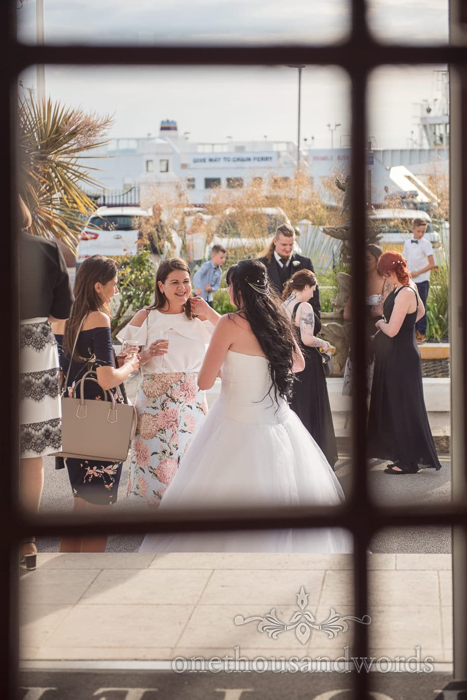 Wedding guests enjoy sunshine outside Haven Hotel with ferry in background